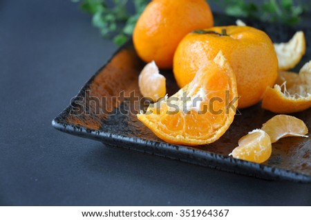 Close up pieces of fresh orange on black plate