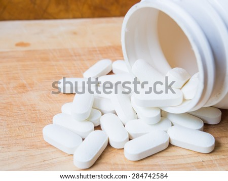 Close up pill bottle spilling pills on to surface - stock photo