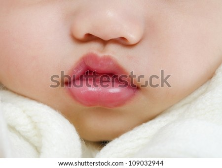 Close up pink lips of a sleeping baby boy with tongue sticking out - stock photo