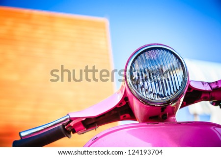 Close-up pink retro motorcycle with colorful background - stock photo