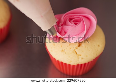 Close up pink rose frosted cupcake being iced horizontal - stock photo