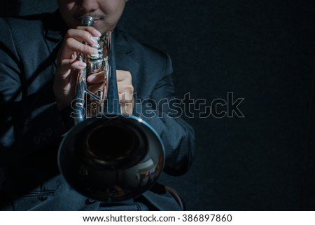 Close up Pipes in the hands of trumpet player on dark,low key image - stock photo