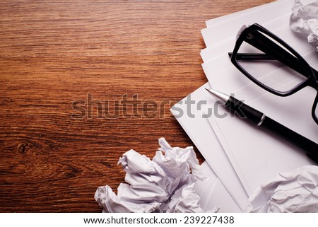 Close up Plain and Crumpled Papers with Pen and Glasses on Top of Brown Wooden Table with Copy Space on Left Side. - stock photo