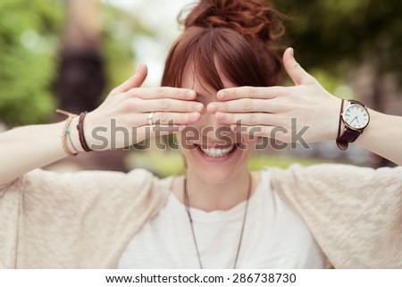 Close up Playful Young Lady Covering her Two Eyes Using her Bare Hands with a Toothy Smile. - stock photo