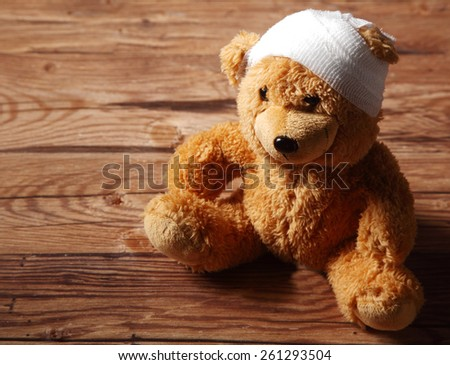 Close up Plush Brown Teddy Bear Toy with Bandaged on the Head Sitting on Top of the Wooden Table - stock photo