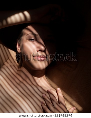 Close up portait of beautiful girl wearing bra. Sunlight through jalousie shines on woman's face.