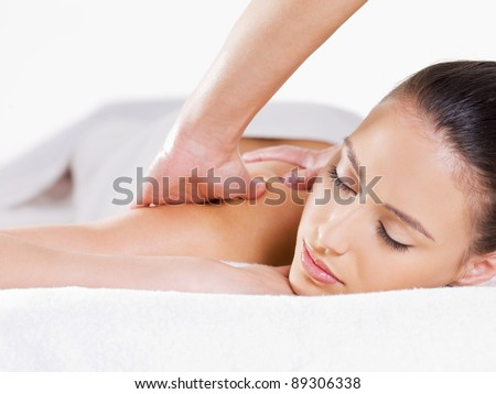 Close-up portait of relaxing woman having massage on her shoulder - white background - stock photo
