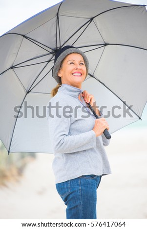 Close up Portrait attractive mature woman happy, relaxed with umbrella at beach on cold overcast day, storm clouds over ocean, blurred background, copy space.