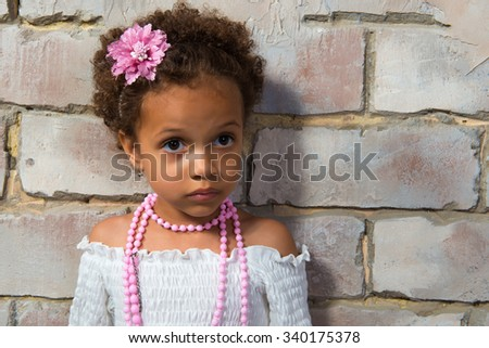 Close-up portrait beautiful african  girl in a white lace dress and pink beads - stock photo