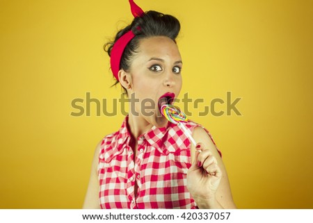 Close up portrait beautiful pin up girl with colorful lollipops, isolated yellow background