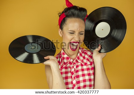 Close up portrait beautiful pin up girl with old vinil records, isolated yellow background
