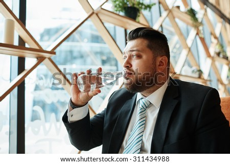 Close up portrait businessman sitting in coffee shop drinking from a bottle of mineral water, with reflections of the city behind him. - stock photo