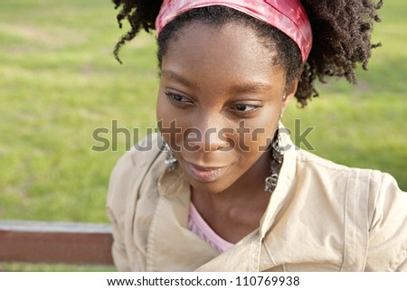 Close up portrait f a young black woman sitting on a bench with green grass in the background, smiling. - stock photo