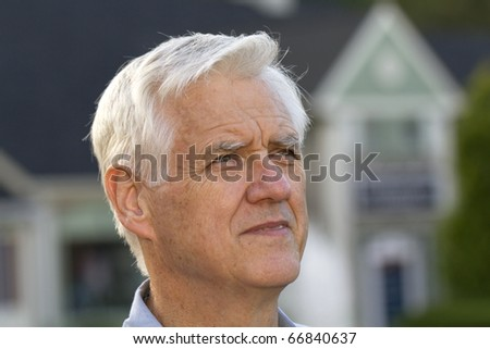 Close up portrait focus on senior man with unfocused house outlines behind him reflect the universal effect of difficult economic housing conditions - stock photo