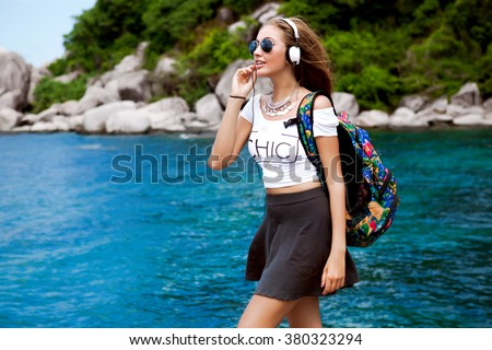 Close up  portrait,fresh beauty cute amazing smiling girl,natural glow make up,floral travel bag,summer vintage outfit, street evening sunlight.fashionable sunglasses,trendy outfit,street style,mp3 - stock photo