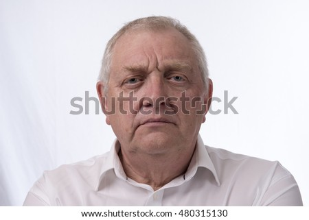 Close up portrait image of a mature man looking annoyed and angry. Taken on a white background.
