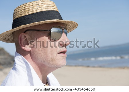 Close up portrait image of a mature man wearing sunglasses and a straw hat. Reflections of the beach can be seen in the glasses.