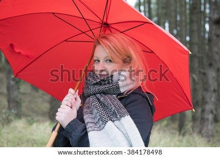 Close up portrait image of a young woman outdoors with a scarf and red umbrella.