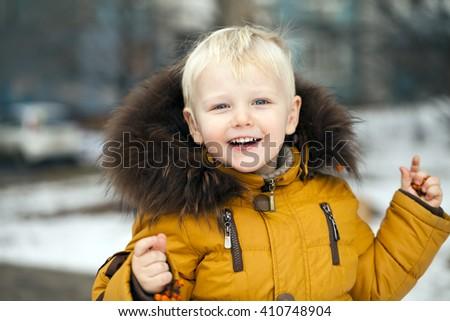 Close up portrait, little baby blonde boy in a winter park - stock photo