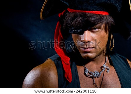 Close-up portrait muscular pirate in the studio on a dark background. A man looking at the camera - stock photo