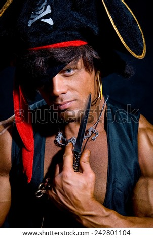 Close-up portrait muscular pirate with a knife on a dark background. A man looking at the camera - stock photo