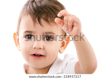 close-up portrait of a amusing little boy in white shirt with hand up on white background