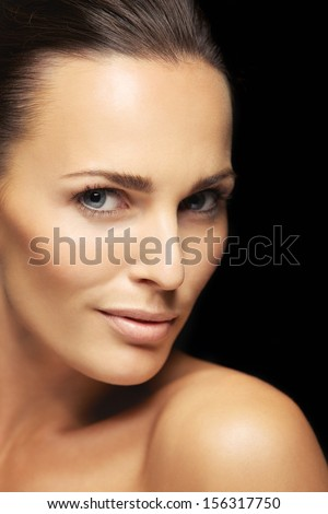 Close-up portrait of a attractive young female with flawless skin looking at camera. Pretty woman with clean and glowing skin isolated on black background
