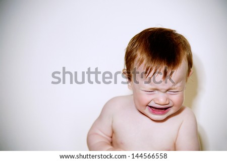 Close up portrait of a baby boy with red hair being unhappy and crying against a white background with a retro style. - stock photo