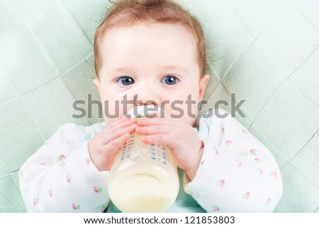 Close up portrait of a baby girl with a milk bottle lying on a green knitted blanket