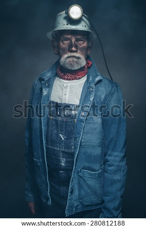 Close up Portrait of a Bearded Senior Male Miner in Denim Jacket and Helmet with Dirty Face, Looking at the Camera Seriously Inside a Fuzzy Studio. - stock photo