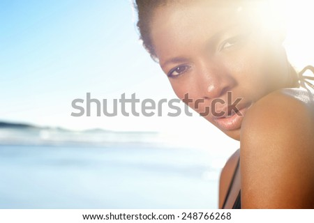 Close up portrait of a beautiful african american female fashion model at the beach - stock photo