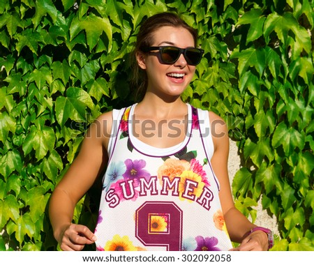 Close-up Portrait of a beautiful and fashionable girl in mirrored sunglasses and trendy wear Posing in the park.Positive emotions.Close up portrait of a happy smiling young woman outside.Floral print. - stock photo