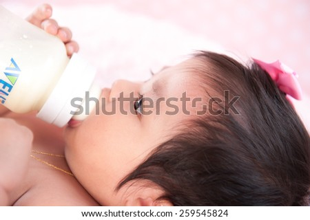 close-up portrait of a beautiful asian baby on pink - stock photo