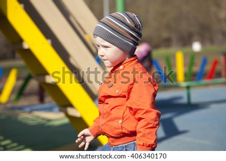 Close up portrait of a beautiful baby boy walking in spring park. Little boy in orange jaket and blue jeans, outdoors - stock photo