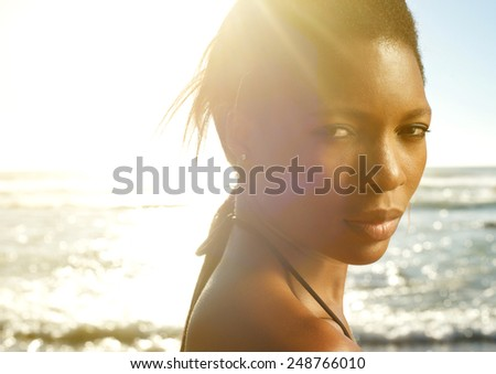 Close up portrait of a beautiful black woman posing at the beach - stock photo