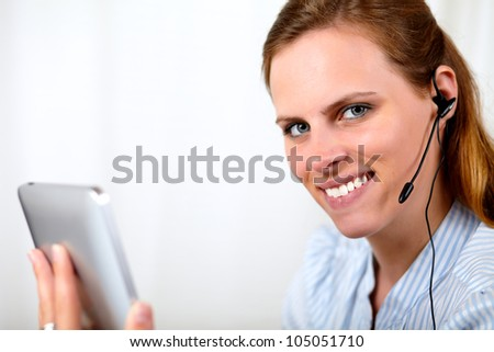 Close up portrait of a beautiful blonde girl smiling while talking and holding a tablet PC - stock photo