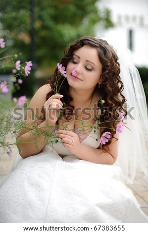 close-up portrait of a beautiful bride smelling delicate flowers in the garden