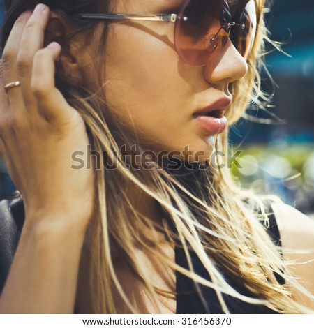 close-up portrait of a beautiful charming girl hipster blonde in sunglasses sexy and posing with full lips in a green dress and earrings with feathers - stock photo