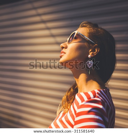 close-up portrait of a beautiful charming girl hipster in  sunglasses blonde with full lips in a striped dress  laughing and posing - stock photo