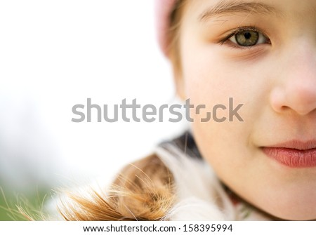 Close up portrait of a beautiful child girl half face in a park looking at camera and being thoughtful during a cold winter day, wearing a warm coat and a pink hat, outdoors. - stock photo