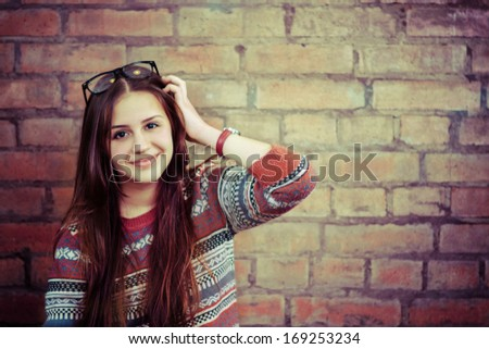 Close up portrait of a beautiful cute teen girl smiling near the brick wall - stock photo