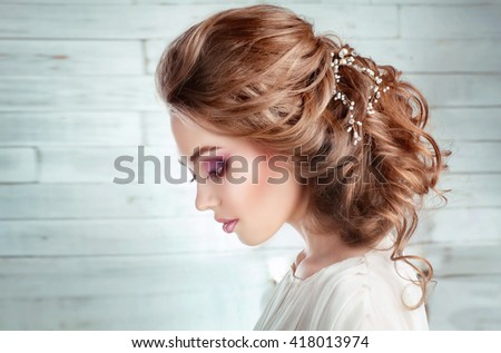 Close up Portrait of a beautiful fashion bride in studio.Perfect make up and hairstyle.Wedding accessories on shiny blonde hair. Pretty sensual young woman dreaming and looking down  - stock photo