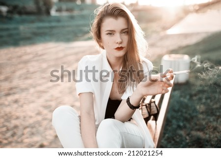 Close-up portrait of a beautiful fashionable girl at sunset near the beach with a cigarette - stock photo