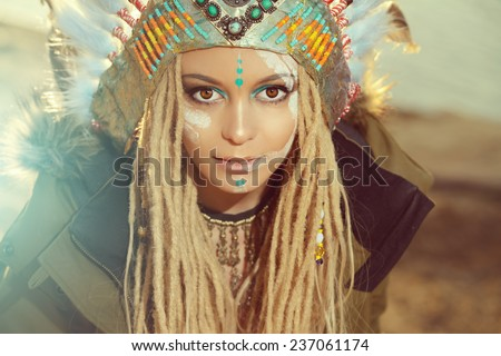 Close-up portrait of a beautiful girl wearing native american indian chief headdress. Western style. Jeans fashion. - stock photo