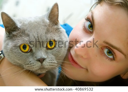 close-up portrait of a beautiful girl with green eyes holding british cat - stock photo