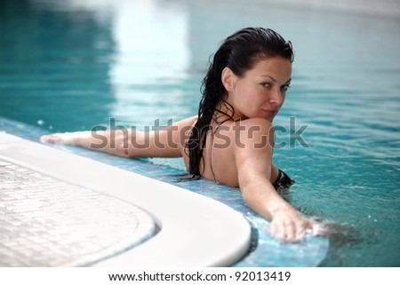 Close up portrait of a beautiful happy woman in swimming pool - stock photo