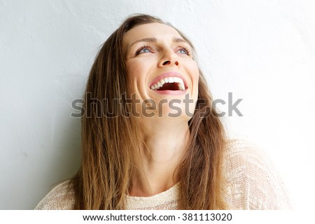 Close up portrait of a beautiful middle aged woman laughing against white background - stock photo