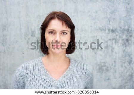 Close up portrait of a beautiful older woman with brown hair standing against gray background - stock photo