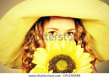 Close-up portrait of a beautiful red-haired girl with sunflower smiling at camera. Summer. Studio shot. - stock photo