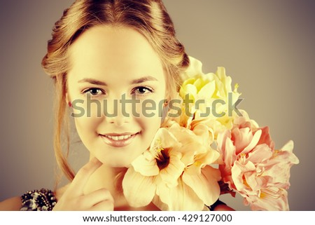 Close-up portrait of a beautiful romantic young woman holding a bouquet of flowers and smiling. Cosmetics, healthcare. Beauty, fashion concept. - stock photo
